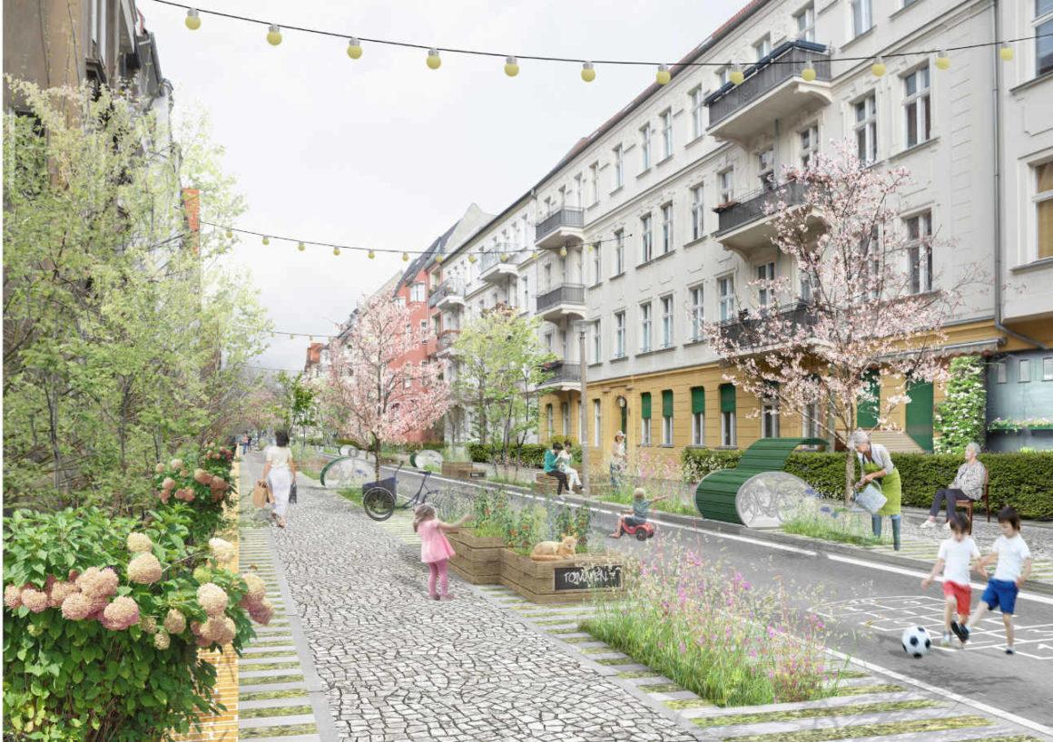 Das Bild zeigt eine verkehrsberuhigte Strasse. Es gibt großzügige Gehwege, Sitzgelegenheiten. Auf der Straße spielen Kinder Fußball. Die Straßenmitte ist mit Pflanztrögen ausgestattet.