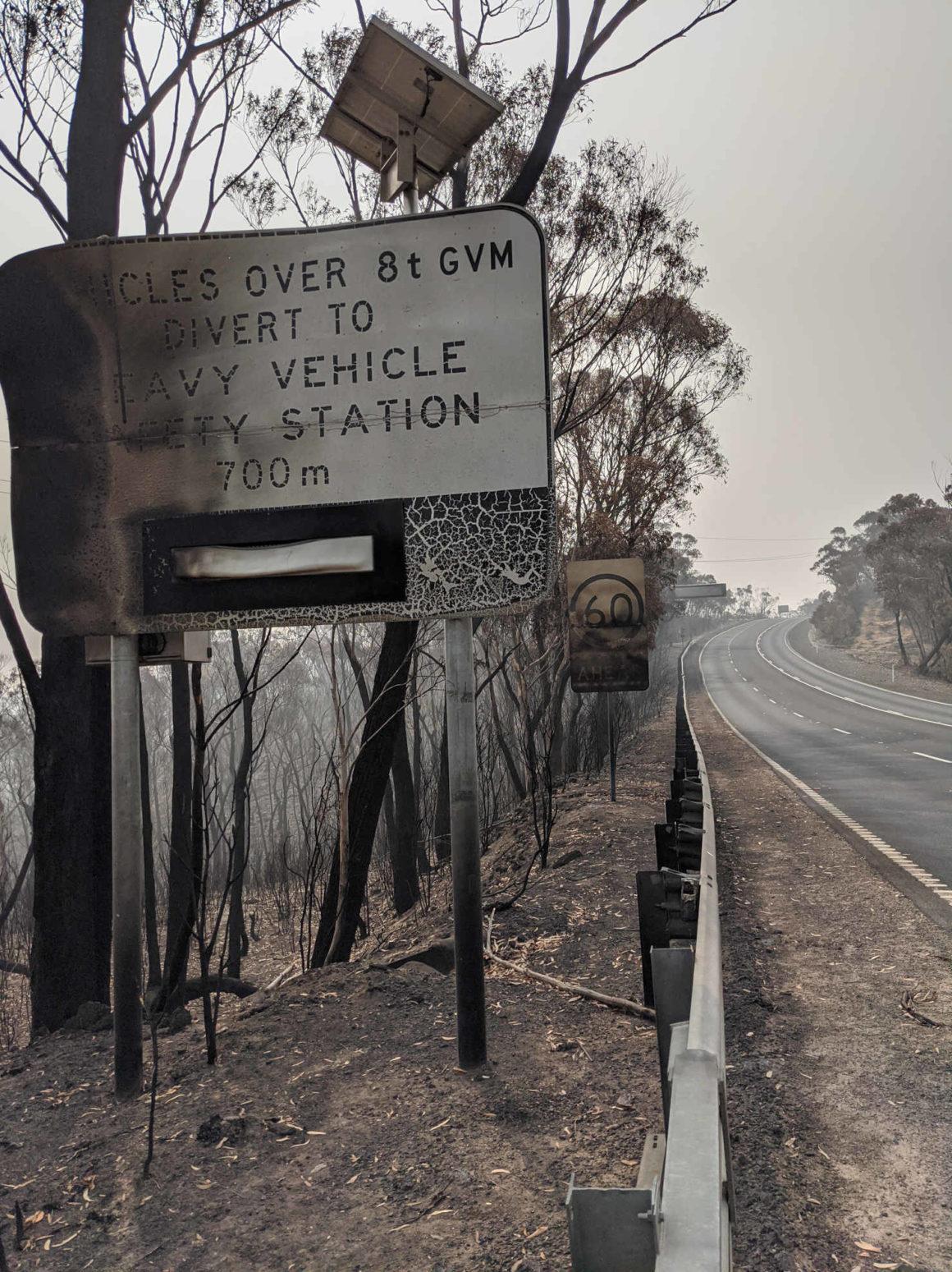 Das Bild zeigt eine Insfrastruktur in Australien die durch ein Großfeuer zerstört wurde. Strassenschilder sind verrusst, verbogen und unlesbar.